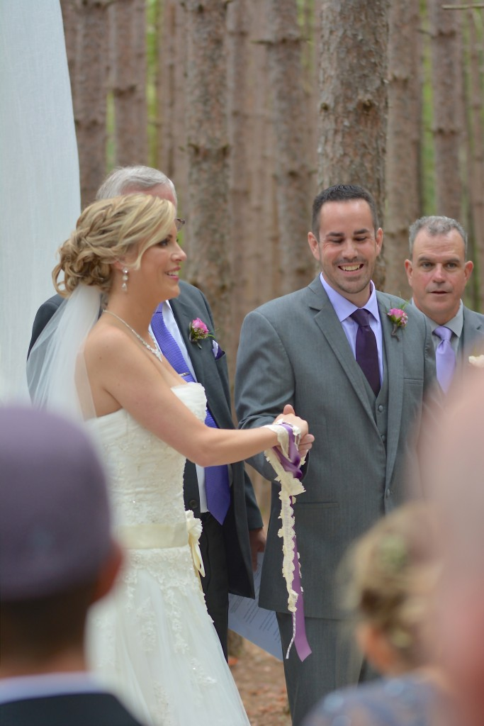 The bride and groom engaged in traditional Handfasting...